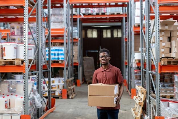 Pozytywny młody afroamerykański pracownik magazynu w okularach chodzący z pudłami nad magazynem i przewożący zamówienie do klienta