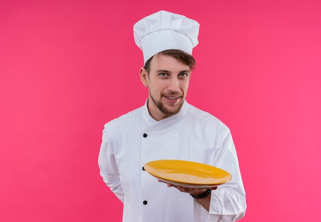 Pozytywny młody brodaty szef kuchni w białym mundurze prezentujący żółty talerz gotowy do jedzenia, patrząc na różową ścianę
