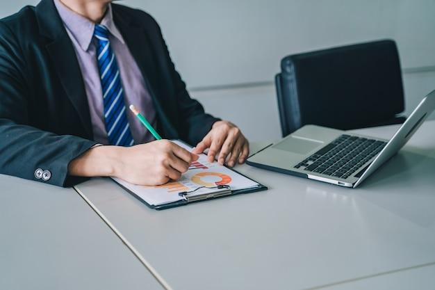 Pozytywny młody człowiek biznesu siedzi i pracuje z dokumentami i laptopem,