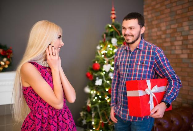 Pozytywny młody człowiek daje swojej pięknej ślicznej żonie prezent w pudełku na nowy rok.