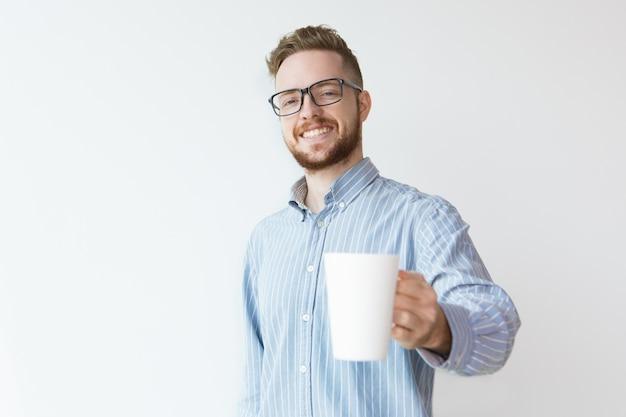 Pozytywny młody człowiek oferuje kawę do kolegi