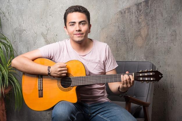 Pozytywny młody człowiek siedzi na krześle i gra na gitarze.