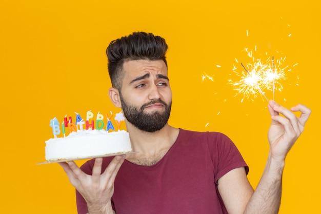 Pozytywny młody człowiek trzyma tort urodzinowy i dwa płonące światła bengalskie pozowanie na żółtym tle.