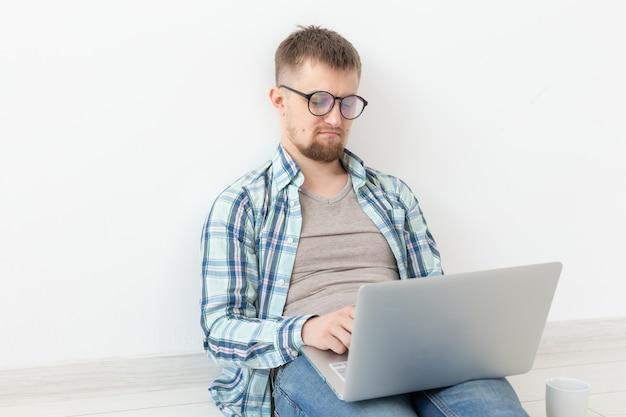 Pozytywny młody człowiek w zwykłych ubraniach i okularach surfuje po internecie za pomocą wi-fi i laptopa