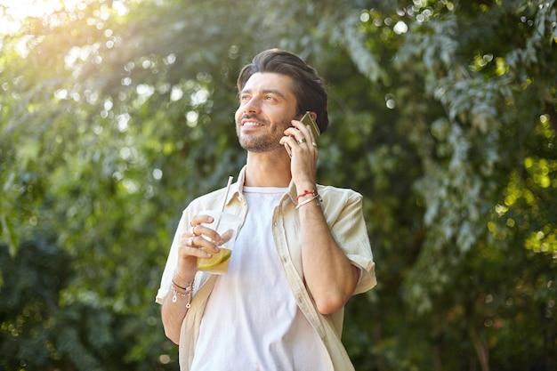 Pozytywny młody ładny mężczyzna z brodą pozuje nad zielonym parkiem miejskim w ciepły słoneczny dzień, dzwoni smartfonem i trzyma plastikowy kubek z lemoniadą