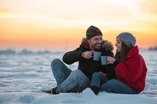 Pozytywny młody mężczyzna i kobieta w ciepłej odzieży wierzchniej z termosem, siedząc na śniegu i pijąc gorący napój na wsi
