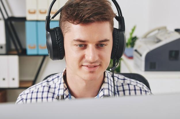 Pozytywny młody operator wsparcia technicznego pomaga użytkownikowi rozwiązać problem, złożyć zamówienie lub wystawić opinię