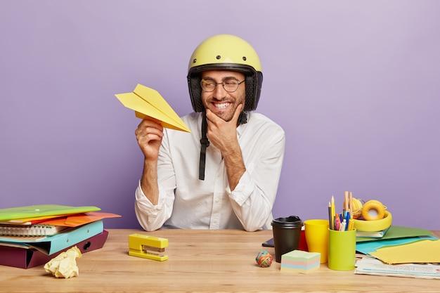 Pozytywny młody pracownik siedzi przy biurku