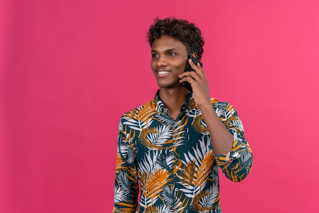 Pozytywny młody przystojny ciemnoskóry mężczyzna z kręconymi włosami w koszulce z nadrukiem liści rozmawia z telefonem komórkowym