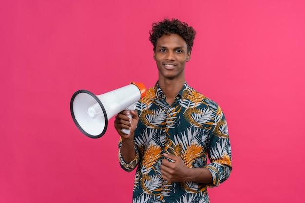 Pozytywny młody przystojny ciemnoskóry mężczyzna z kręconymi włosami w koszulce z nadrukiem liści trzyma megafon na różowym tle