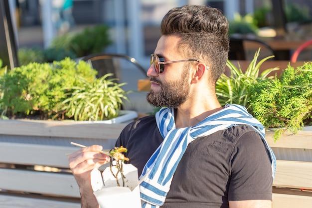 Pozytywny młody stylowy arabski facet je chiński makaron w parku podczas przerwy w pracy. pojęcie odpoczynku i zdrowej przekąski.