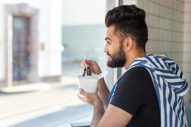 Pozytywny młody stylowy facet jedzenie makaronu chińskiego w kawiarni podczas przerwy w pracy. pojęcie odpoczynku i zdrowej przekąski.