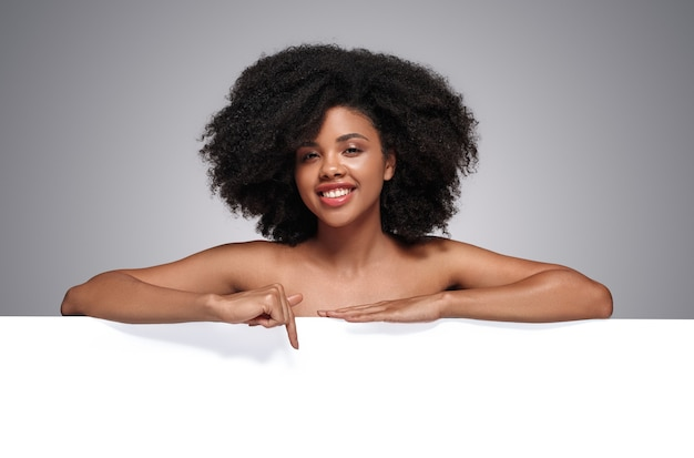 Pozytywny model african american, wskazując na pusty transparent