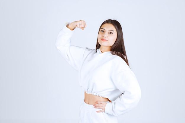 Pozytywny model młoda dziewczyna pokazując jej biceps.