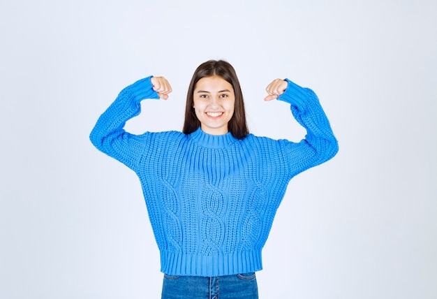 Pozytywny model młoda dziewczyna wskazując na jej biceps.