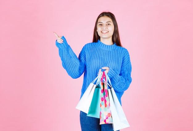Pozytywny model młoda dziewczyna z torby na zakupy, wskazując na różowej ścianie.