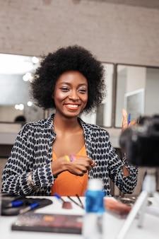 Pozytywny nastrój. niesamowita kobieta z kręconymi włosami wyglądająca pozytywnie mówiąc o nowej kolekcji kolorystycznej