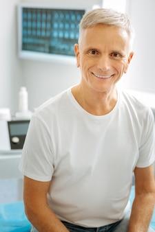 Pozytywny nastrój. szczęśliwy miły zachwycony mężczyzna uśmiecha się i patrzy na ciebie siedząc w gabinecie lekarskim