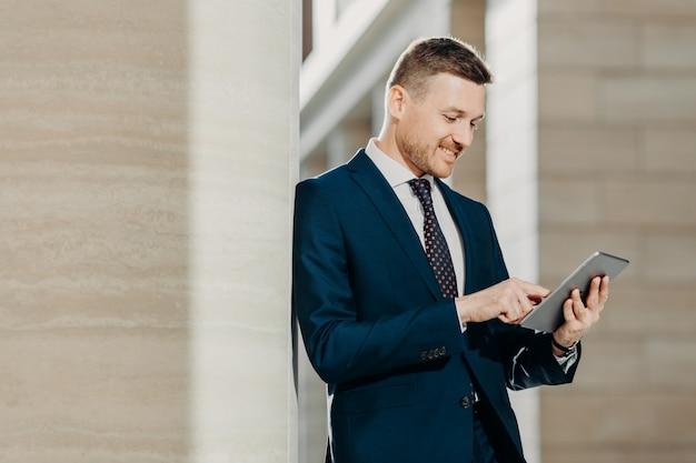 Pozytywny nieogolony biznesmen czyta wiadomości w internecie na stronie internetowej