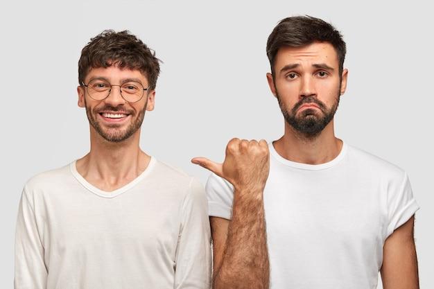 Pozytywny nieogolony młody człowiek ma zadowolony wyraz twarzy, będąc w dobrym nastroju, brodaty facet z niezadowoleniem wskazuje na przyjaciela