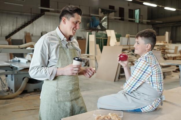 Pozytywny ojciec w średnim wieku w fartuchu, pijący kawę podczas przerwy obiadowej z synem w stolarni