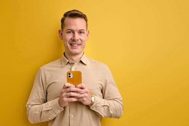 Pozytywny optymistyczny facet trzymając smartfon w rękach, uśmiechając się do kamery na białym tle na żółtej ścianie.