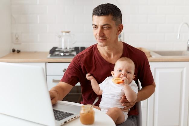Pozytywny optymistyczny przystojny mężczyzna freelancer ubrany w bordową koszulkę, pozujący w białej kuchni, siedzący przed laptopem z dzieckiem w rękach i pracujący online.