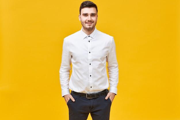 Pozytywny, pewny siebie młody pracownik biurowy rasy kaukaskiej ubrany w białą formalną koszulę i klasyczne spodnie z paskiem, mający szczęśliwy wyraz twarzy, trzymający ręce w kieszeniach i uśmiechający się radośnie