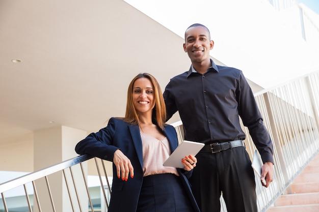 Pozytywny pomyślny profesjonalista pozuje w centrum biznesu
