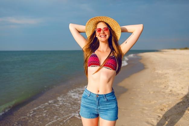 Pozytywny portret ładnej młodej kobiety cieszy się wakacjami w pobliżu morza, samotną plażą wokół, podróżowaniem, zdrowym szczupłym ciałem, kapeluszem bikini i okularami przeciwsłonecznymi