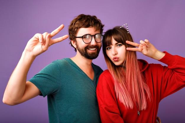 Pozytywny portret szalonej młodej pary hipster, która bawi się razem, pokazując gest pokoju, śmiejąc się i krzycząc, nosząc stylową bluzę z kapturem i koszulkę, zdjęcie rodziny i przyjaciół