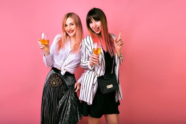 Pozytywny portret wewnętrzny dwóch stylowych eleganckich ładnych kobiet bawiących się na imprezie, pijących smacznego szampana i tańczących, wieczorowych strojów koktajlowych i różowej ściany