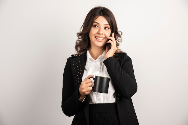 Pozytywny pracownik rozmawia przez telefon trzymając herbatę