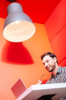 Pozytywny programista. pozytywnie pracowity młody programista siedzący na czerwonej ścianie i patrząc na ekran nowoczesnego urządzenia