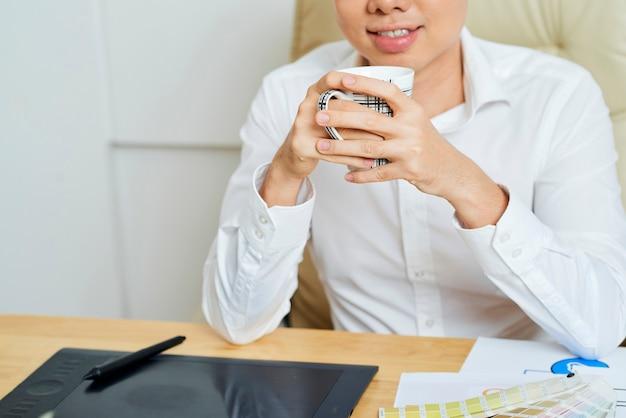 Pozytywny Projektant Interfejsu Użytkownika Pijący Filiżankę Kawy Po Zakończeniu Pracy Nad Dużym Projektem Premium Zdjęcia