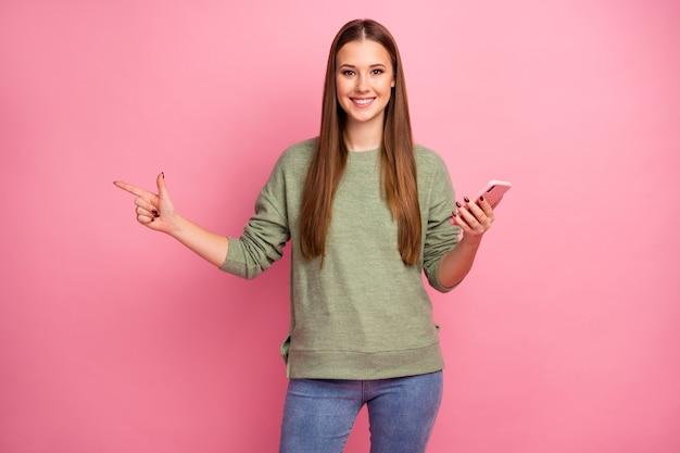 Pozytywny promotor wesoły dziewczyna używa smartfona wskazuje palec copyspace
