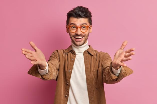 Pozytywny, przyjazny europejczyk podnosi ręce, gdy ktoś wyciąga ręce w geście powitania