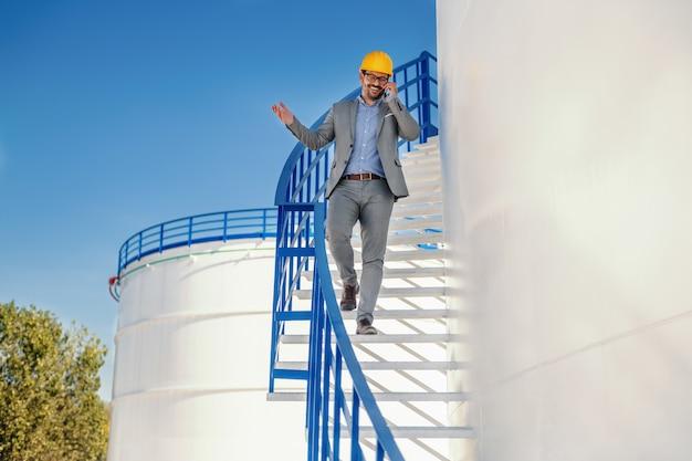 Pozytywny przystojny biznesmen kaukaski w garniturze z kaskiem na głowie schodząc po schodach i rozmowę telefoniczną z ważnym klientem. zewnętrzna rafineria. w tle jest zbiornik oleju.