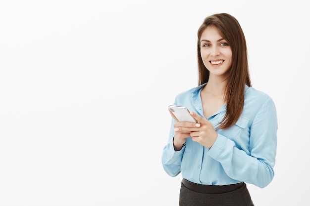 Pozytywny przystojny brunetka bizneswoman pozuje w studiu