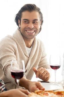 Pozytywny przystojny mężczyzna rasy mieszanej z zarostem, siedzący przy stole z kieliszkami do wina i rozmawiający z przyjaciółmi na przyjęciu