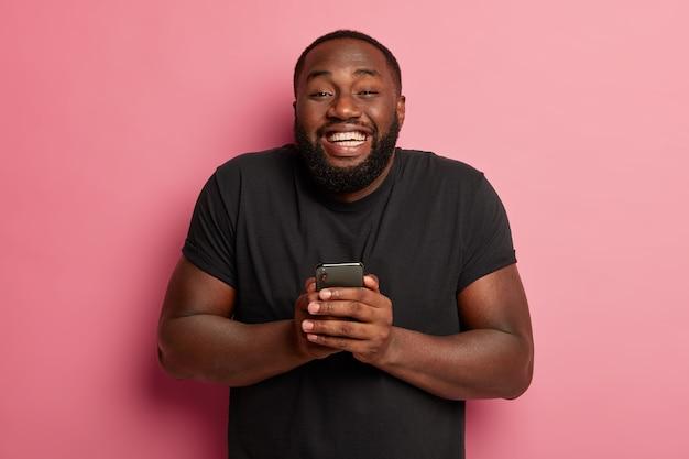 Pozytywny pulchny mężczyzna z gęstą brodą, dzieli się świetnymi wiadomościami w sieciach społecznościowych z przyjacielem, będąc w siódmym niebie od szczęścia, trzyma nowoczesny smartfon