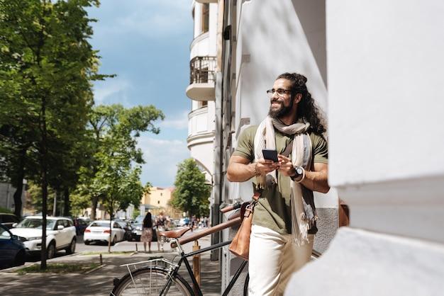 Pozytywny radosny człowiek patrząc na ulicę, stojąc ze swoim smartfonem