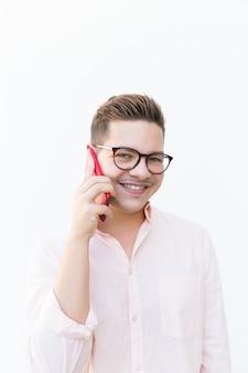 Pozytywny radosny facet z telefonem komórkowym pozuje i ono uśmiecha się