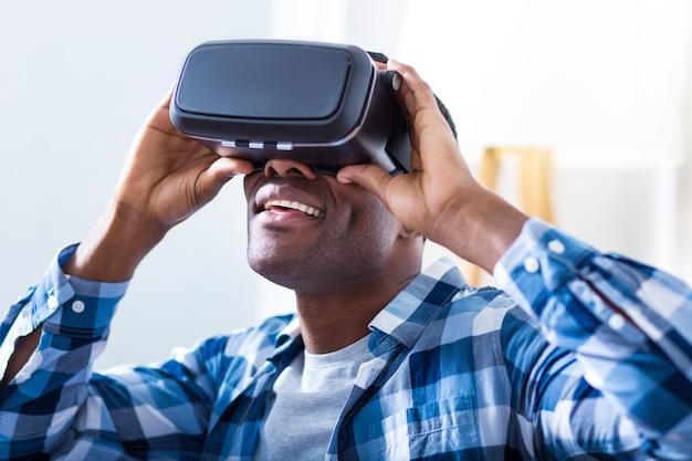 Pozytywny radosny miły mężczyzna trzyma okulary 3d i uśmiecha się, będąc podekscytowanym futurystyczną technologią