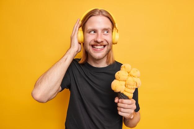 Pozytywny rudy brodaty mężczyzna trzyma rękę na słuchawkach trzyma pyszne lody cieszy się ulubioną muzyką przez słuchawki, ubrany niedbale na białym tle nad żółtą ścianą. hipsterski facet z gelato
