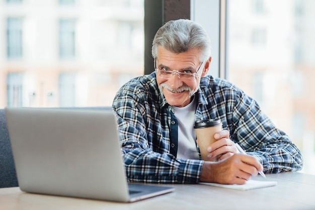 Pozytywny stary biznesmen pracujący na laptopie w kawiarni pijącej kawę