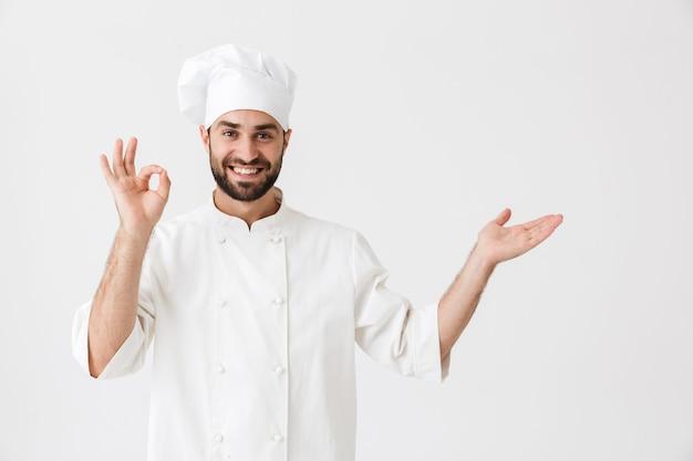 Pozytywny szczęśliwy młody kucharz pozowanie w mundurze zrobić w porządku gest pokazując copyspace.