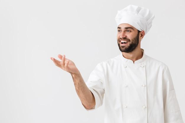 Pozytywny szczęśliwy młody kucharz pozowanie w mundurze.