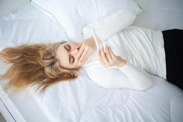 Pozytywny test ciążowy. młoda kobieta czuje się przygnębiona i smutna po obejrzeniu wyniku testu ciążowego w domu