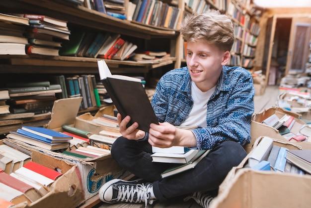 Pozytywny uczeń siedzi na podłodze w starej bibliotece publicznej i czyta książki.